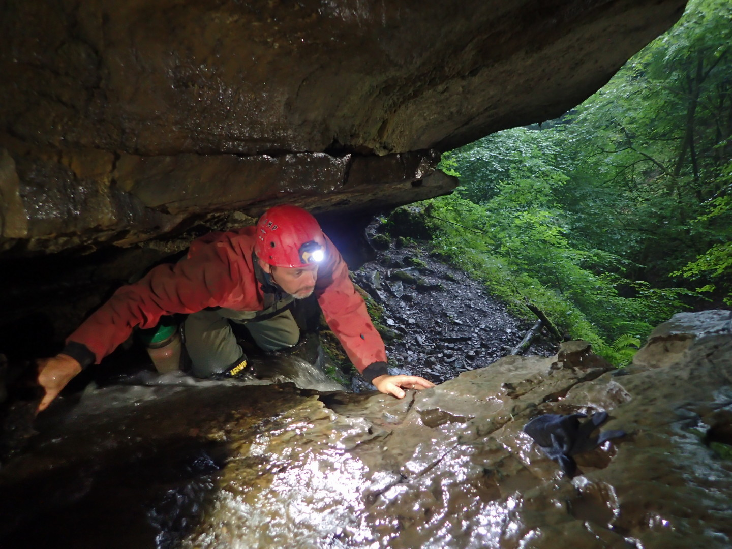 Huw D climbing into cave